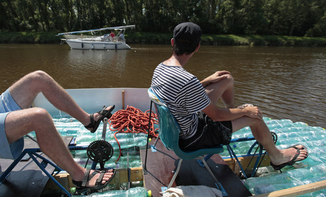 A yacht passes by as Jan Kara (R) and Jan Brand pedal their boat, made with plastic bottles, on the Elbe river near Kostelec nad Labem July 15, 2014. (Photo by David W. Cerny/Reuters)