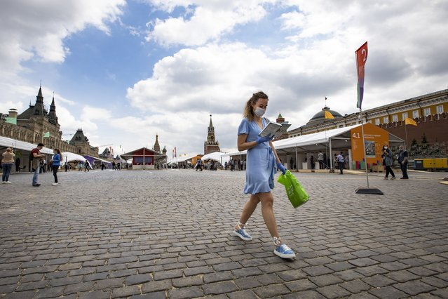 A woman read a book as she walks at an outdoor book market in the Red Square with GUM, State Department store at left, St. Basil's Cathedral, center and the Kremlin Wall, right, in Moscow, Russia, Saturday, June 6, 2020. Muscovites clad in face masks and gloves ventured into Red Square for an outdoor book market, a small sign of the Russian capital's gradual efforts to open up amid coronavirus concerns. (Photo by Alexander Zemlianichenko/AP Photo)