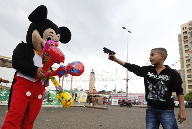 A Syrian refugee boy points a plastic toy pistol at a man in a Mickey Mouse costume on the first day of Eid al-Adha at a park in Beirut October 26, 2012. Muslims around the world celebrate Eid al-Adha, marking the end of the haj, by slaughtering sheep, goats, cows and camels to commemorate Prophet Abraham's willingness to sacrifice his son Ismail on God's command. (Photo by Jamal Saidi/Reuters)