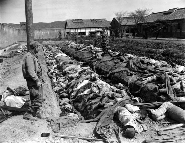 Bodies of some 400 Korean civilians lie in and around trenches in Taejon's prison yard during the Korean War, Sept. 28, 1950. The victims were bound and slain by retreating Communist forces before the 24th U.S. Division troops recaptured the city Sept. 28. Witnesses said that the prisoners were forced to dig their own trench graves before the slaughter.  Looking on, at left, is Gordon Gammack, war correspondent of the Des Moines Register and Tribune. (Photo by James Pringle/AP Photo)