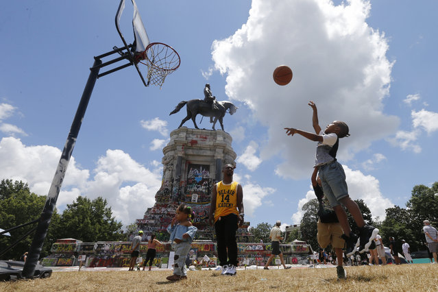 Isaiah Bowen, right, takes a shot as his dad, Garth Bowen, center, looks on at a basketball hoop in front of the statue of Confederate General Robert E. Lee on Monument Avenue Sunday June 21, 2020, in Richmond, Va. A judge extended an injunction delaying the removal of the statue by the state. The statue had become a focal point for the Black Lives Matter movement in Richmond. (Photo by Steve Helber/AP Photo)