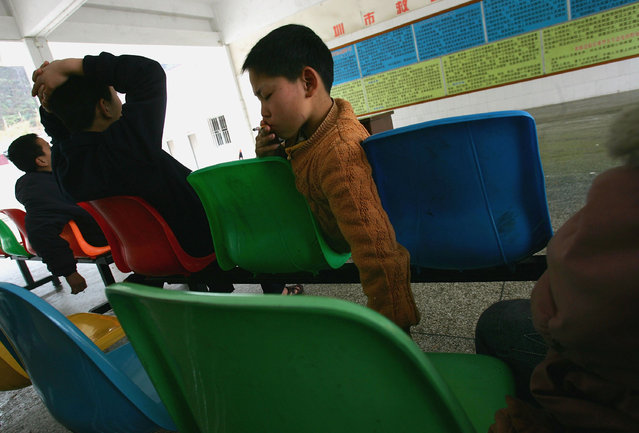 A kid from Sichuan provice smokes a cigarette at an assistance center February 23, 2005 in Shenzhen, Guangdong Province, China. (Photo by Cancan Chu/Getty Images)