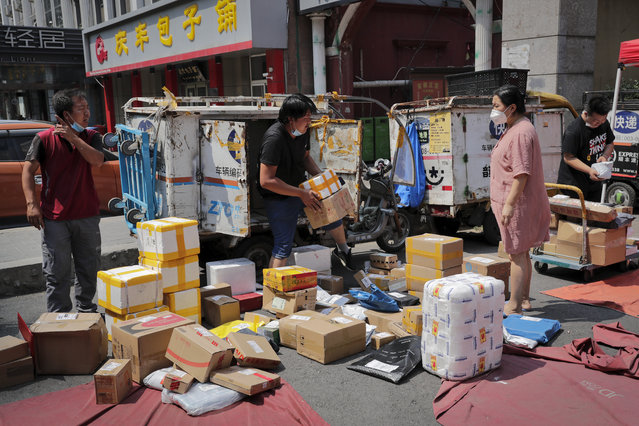 A woman wearing a protective face mask to help curb the spread of the new coronavirus waits for a delivery worker sorting out her parcel at a collection point outside an apartment in Beijing, Sunday, June 21, 2020. According to state media reports, nearly one hundred thousand delivery workers have to accept the nucleic acid testing, a countermeasure to prevent the spread of the virus in the capital city. (Photo by Andy Wong/AP Photo)