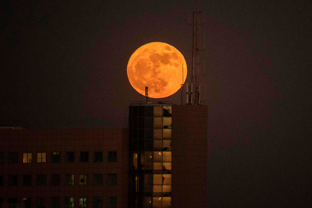 "The ""supermoon"" rises over a building in the Israeli city of Netanya, on December 3, 2017. The lunar phenomenon occurs when a full moon is at its closest point to earth. (Photo by Jack Guez/AFP Photo)"