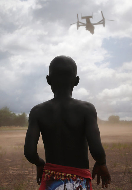A boy watches as a U.S. Marine MV-22 Osprey tiltrotor departs the site of an Ebola treatment center under construction on October 15, 2014 in Tubmanburg, Liberia. The center is the first of 17 Ebola treatment centers being built by Liberian forces under American supervision as part of Operation United Assistance to combat the Ebola epidemic. (Photo by John Moore/Getty Images)