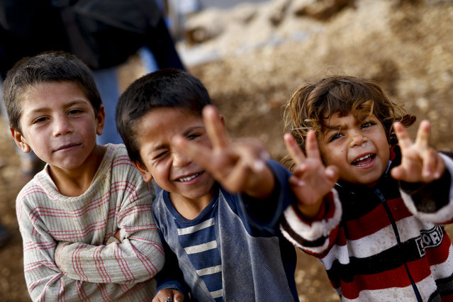 Kurdish refugee children from the Syrian town of Kobani show victory signs in a camp in the southeastern town of Suruc on the Turkish-Syrian border, October 19, 2014. (Photo by Kai Pfaffenbach/Reuters)