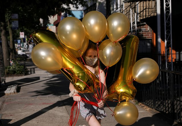 Lydia Hassebroek carries balloons for her birthday party in Brooklyn as New York slowly reopens during the continued coronavirus outbreak, July 12, 2020. (Photo by Caitlin Ochs/Reuters)