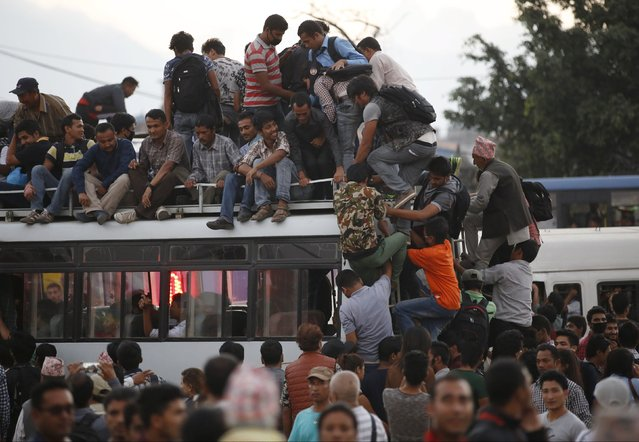 Passengers take a ride on an overcrowded bus as limited public transportation operates in the city during the ongoing oil and fuel crisis in Kathmandu, Nepal September 29, 2015. (Photo by Navesh Chitrakar/Reuters)