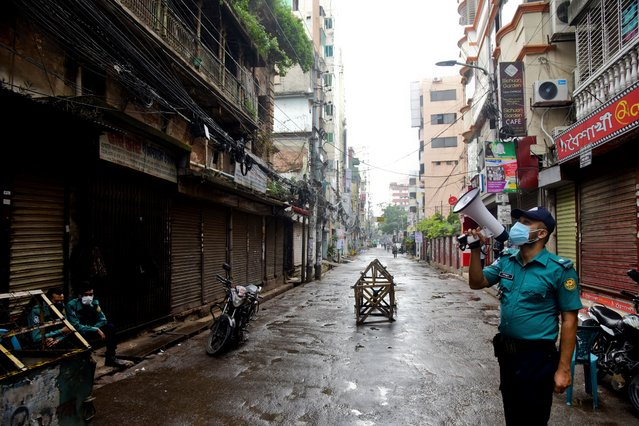 Policeman aware to general people for stay home as they patrolling on the streetsin a government imposed coronavirus red zone with maximum infection risk at Wari in Dhaka, Bangladesh, on July 04, 2020. (Photo by Mamunur Rashid/NurPhoto via Getty Images)