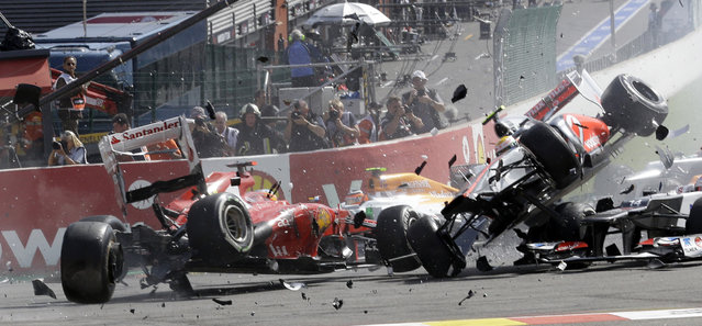 Ferrari driver Fernando Alonso of Spain, left, crashes with McLaren Mercedes driver Lewis Hamilton of Britain, airborne right,  during the first lap of the Belgium Formula One Grand Prix in Spa-Francorchamps circuit, Belgium, Sunday, September 2, 2012. (Photo by Luca Bruno/AP Photo)