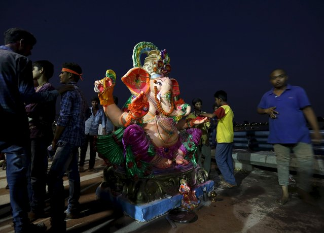 Devotees stand around an idol of the Hindu god Ganesh, the deity of prosperity, before its immersion during the ten-day-long Ganesh Chaturthi festival in Ahmedabad, India, September 23, 2015. (Photo by Amit Dave/Reuters)