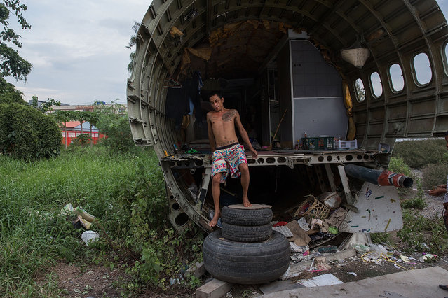 A Thai man climbs down from his home in a disused airplane on September 12, 2015 in Bangkok, Thailand. 3 impoverished Thai families have begun living in disused airplanes on a private field. The families, who collect and recycle garbage earning a few dollars a day, can't afford to rent and prefer to stay in the planes. (Photo by Taylor Weidman/Getty Images)