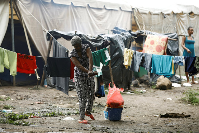 An African migrant stranded in Costa Rica washes her clothes in a makeshift camp at the border between Costa Rica and Nicaragua, in Penas Blancas, Costa Rica, September 8, 2016. (Photo by Juan Carlos Ulate/Reuters)