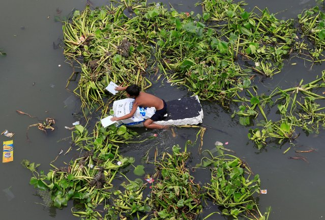 A boy wades through a polluted river using a makeshift raft made of styrofoam to collect reusable items at a Manila bay in Baseco, Tondo city, metro Manila, Philippines August 1, 2016. (Photo by Romeo Ranoco/Reuters)