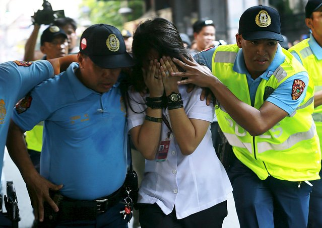 Policemen assist one of the passengers to safety during a robbery incident inside a public bus in Manila October 8, 2015. (Photo by Romeo Ranoco/Reuters)