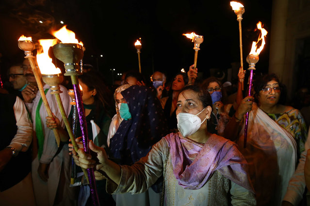 People hold torches as they mark Pakistan Independence Day celebrations in Karachi, Pakistan, 13 August 2020. Millions of Pakistanis celebrates the 73rd independence anniversary from British rule on 14 August 2020. (Photo by Rehan Khan/EPA/EFE)