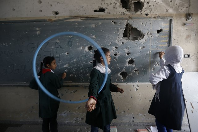 Palestinian girls play inside their school which was destroyed during the 50 days of conflict between Israel and Hamas last summer, in the Shejaiya neighborhood of Gaza City, on November 5, 2014. A leading human rights group has accused Israel of committing war crimes during this summer's war in Gaza. (Photo by Mohammed Abed/AFP Photo)