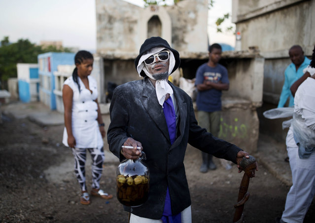 """A man invokes a """"Gede"""" spirit during Haiti's annual Voodoo festival Fete Gede, at the National Cemetery in Port-au-Prince, on November 1, 2017. Revelers stream into cemeteries across the country, in a two-day celebration, to honor Baron Samedi, the guardian of the dead and ruler of the graveyard, and the rest of the Gede spirits which represent death and fertility. (Photo by Dieu Nalio Chery/AP Photo)"""