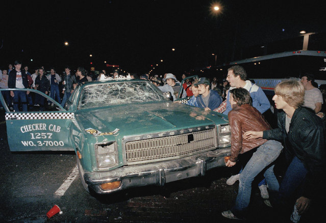 In this October 14, 1984 file photo, a crowd attempts to topple a damaged taxi car outside Detroit's Tiger Stadium after the Detroit Tigers defeated the San Diego Padres to win the 1984 World Series baseball championship. (Photo by AP Photo)