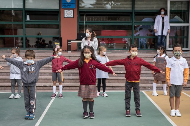 First grade students wearing protective face masks stretch their arms out to learn about social distancing during a physical education class at the Florya Ugur College on September 21, 2020 in Istanbul, Turkey. For the first time since schools closed on March 16, due to the coronavirus outbreak, kindergarten and first grade students were allowed to return for in-person classes at schools across Turkey. The one day a week classes are voluntary and restarted amid strict coronavirus precautions. As coronavirus cases continue to spike around the globe many families continue to opt for online classes. (Photo by Chris McGrath/Getty Images)