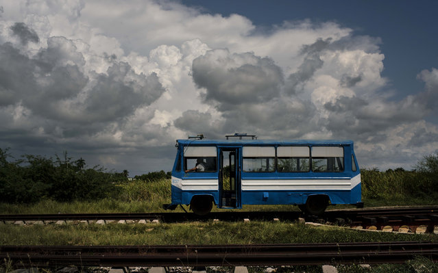 "In this October 11, 2015 photo, a train wagon made to look like a bus, moves along the tracks on the outskirts of Trinidad, Cuba. This train, known as a ""train auto motor"", moves passengers to and from the outskirts of the city. (Photo by Ramon Espinosa/AP Photo)"