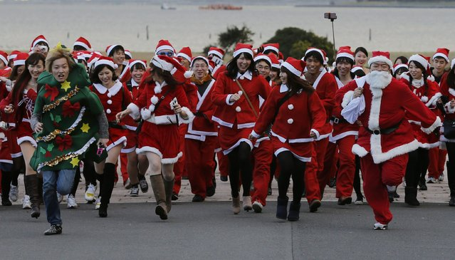 People dressed in Santa Claus costumes participate in the Tokyo Santa Run at a park in Tokyo December 6, 2014. Hundreds of people wearing costumes participated in the 2.5km (1.5 miles) charity run on Saturday to raise funds for children ahead of the upcoming Christmas season. (Photo by Yuya Shino/Reuters)