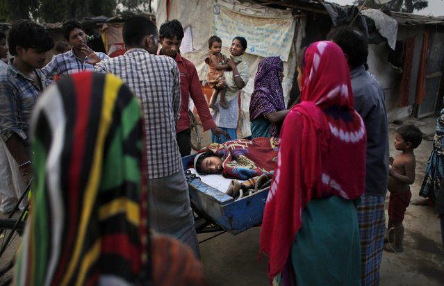 In this October 29, 2014 photo, Marjina, 12, is taken to a hospital on a cart used to carry trash, outside their rented shanty on the outskirts of New Delhi, India. (Photo by Altaf Qadri/AP Photo)