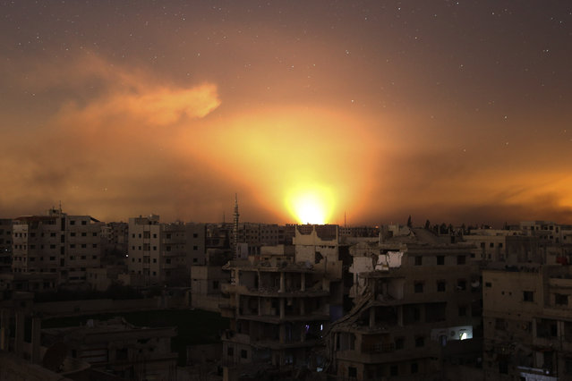 A general view shows explosions lighting the sky following regime air strikes on Arbin, in the rebel enclave of Eastern Ghouta on the outskirts of Damascus on March 12, 2018. (Photo by Abdulmonam Eassa/AFP Photo)
