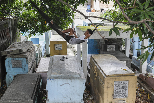 A man who lives inside the North Cemetery relaxes on his hammock on top of tombs on Wednesday, October 28, 2020, in Manila, Philippines. The government has ordered all private and public cemeteries, memorial parks, and columbariums to be closed from Oct. 29 to Nov. 4, 2020, to prevent people from gathering during the observance of the traditionally crowded All Saints Day and to help curb the spread of the coronavirus. (Photo by Aaron Favila/AP Photo)