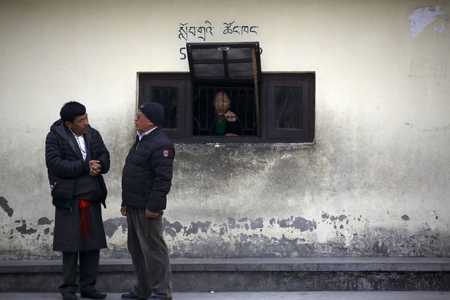 A Tibetan woman looks out a window as men speak with each other during a function organised by the Tibetan Refugee Community in Nepal,commemorating the 25th Anniversary of the Nobel Peace Prize conferment to exiled Tibetan spiritual leader Dalai Lama and the 66th International Human Rights Day in Kathmandu December 10, 2014. (Photo by Navesh Chitrakar/Reuters)
