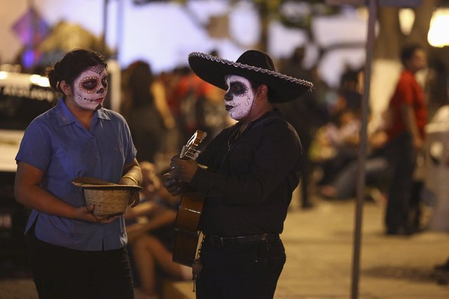 A street musician and his aide, both with calavera face paint for Day of the Dead celebration, perform in Merida, Mexico, October 31, 2015. (Photo by Lorenzo Hernandez/Reuters)