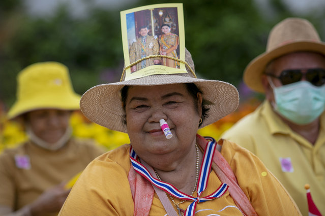 A supporter of the monarchy with an inhaler stuck in her nose, displays an image of King Maha Vajiralongkorn and Queen Suthida as she joins a gathering in front of the Grand Place in Bangkok, Thailand, Sunday, November 1, 2020. Hundreds of royalists gathered close to the Grand Palace in which King Maha Vajiralongkorn is scheduled to visit for a Buddhist religious ceremony. (Photo by Wason Wanichakorn/AP Photo)