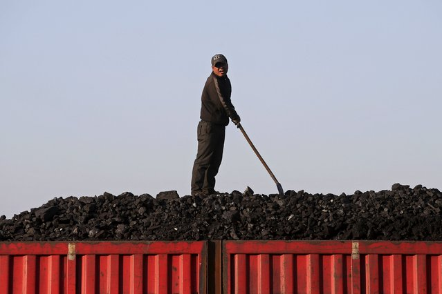 A worker speaks as he loads coal on a truck at a depot near a coal mine from the state-owned Longmay Group on the outskirts of Jixi, in Heilongjiang province, China, October 24, 2015. (Photo by Jason Lee/Reuters)