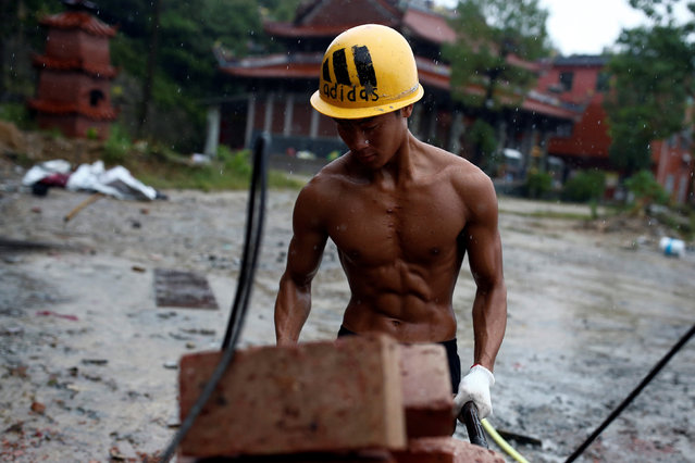 Worker Shi Shenwei pulls a wheelbarrow at the construction site of a Buddhist temple in the village of Huangshan, near Quanzhou, Fujian Province, China, September 28, 2016. (Photo by Thomas Peter/Reuters)
