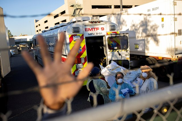 An El Paso County Sheriff's Officer tries to block photographs from being taken as bodies are moved to refrigerated trailers, deployed during a surge of coronavirus deaths, outside the County of El Paso Medical Examiner's Office in El Paso, Texas, November 16, 2020. (Photo by Ivan Pierre Aguirre/Reuters)