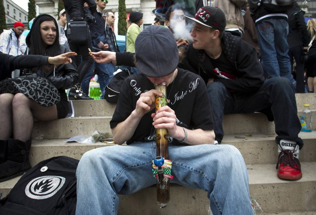 A teenager smokes marijuana out of a bong while with friends at the Vancouver Art Gallery during the annual 4/20 day, which promotes the use of marijuana, in Vancouver, British Columbia April 20, 2013. (Photo by Ben Nelms/Reuters)