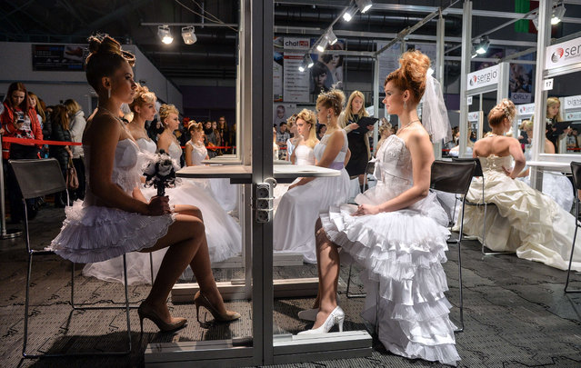Models wearing wedding gowns participate in a national championship on hairdressing, make-up and nail design in Minsk on November 6, 2015. (Photo by Maxim Malinovsky/AFP Photo)