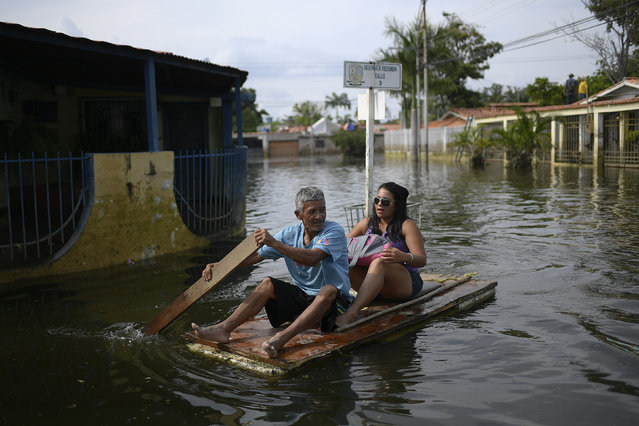 A man utilizes a door as a makeshift raft as he transports a woman through the inundated streets of the Mata Redonda neighborhood of Maracay, Venezuela, Wednesday, October 21, 2020. Heavy rainfall in the central Venezuelan state of Aragua caused the Madre Vieja River to overflow flooding several neighborhoods. (Photo by Matias Delacroix/AP Photo)
