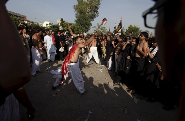 A Pakistani Shi'ite Muslim man flagellates himself with others during a Muharram procession ahead of Ashura in Islamabad, Pakistan, October 23, 2015. (Photo by Faisal Mahmood/Reuters)