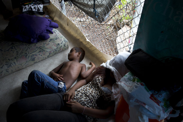In this Monday, August 24, 2015 photo, a boy and woman sleep in their makeshift tent at a homeless encampment in the Kakaako district of Honolulu. There are estimated 7,620 homeless people living on the streets in Hawaii. (Photo by Jae C. Hong/AP Photo)