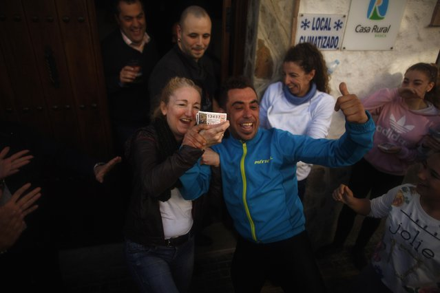 """A woman holds her lottery ticket with a winning number of Spain's Christmas Lottery """"El Gordo"""", as she celebrates with other winners in El Gastor, near Cadiz, southern Spain, December 22, 2014. (Photo by Jon Nazca/Reuters)"""