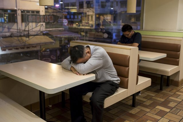 A man sleeps at a 24-hour McDonald's restaurant in Hong Kong, China November 11, 2015. (Photo by Tyrone Siu/Reuters)