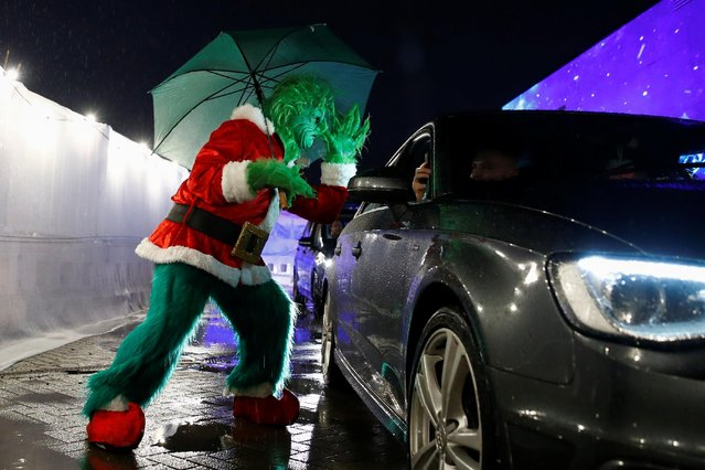 A person dressed as The Grinch performs as people attend the ChristmasCity drive-in cinema showing of the movie Home Alone, amid the outbreak of the coronavirus disease (COVID-19) in Manchester, Britain, December 3, 2020. (Photo by Jason Cairnduff/Reuters)