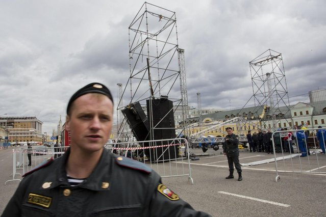 A Russian policeman secures the area, as rescuers try to free the body of a man killed by a collapsed construction of the stage for a major protest rally in Bolotnaya Square in Moscow, Russia, Monday May 6, 2013. Moscow police say a man helping construct the stage for a major protest rally has died after a column of sound equipment collapsed. The accident at midday Monday came just a few hours before opponents of President Vladimir Putin were to gather for a demonstration. The rally marks the one-year anniversary of a protest on the eve of Putin's inauguration that ended in clashes between police and demonstrators. (AP Photo/Yevgeny Feldman)