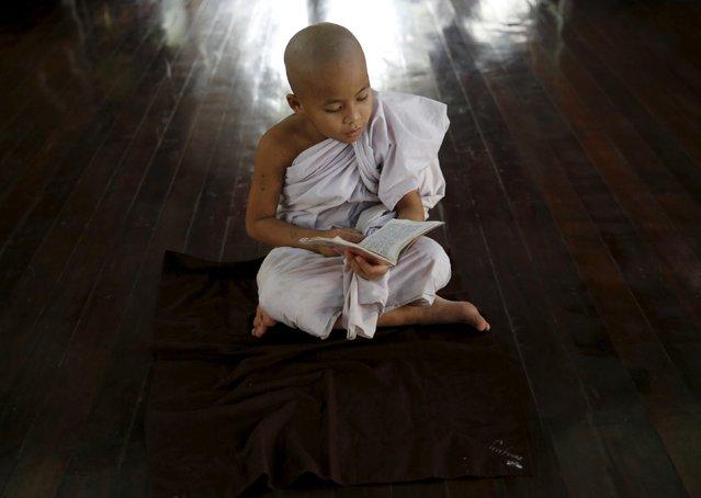 Pre-novice monk Zarnayar, 11-years-old, studies Buddhist texts at a monastery outside Mandalay, Myanmar, November 10, 2015. (Photo by Olivia Harris/Reuters)