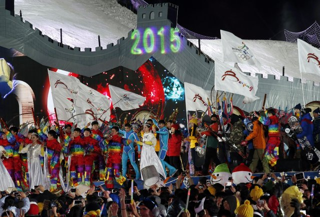 "Performers celebrate the arrival of the new year in front of the National Stadium, also known as the ""Bird's Nest"", during a new year's countdown event to celebrate the arrival of the new year and in wishing winning the bid to host the 2022 Winter Olympic Games, in Beijing January 1, 2015. (Photo by Kim Kyung-Hoon/Reuters)"