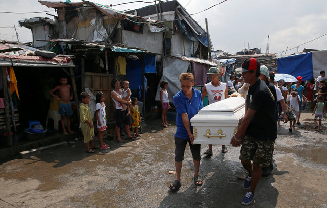 Neighbours watch as mourners carry the coffin of Vicente Batiancila, whom police said was among five victims of drug related killings three weeks ago, during his funeral in Navotas, Metro Manila in the Philippines, October 23, 2016. (Photo by Erik De Castro/Reuters)