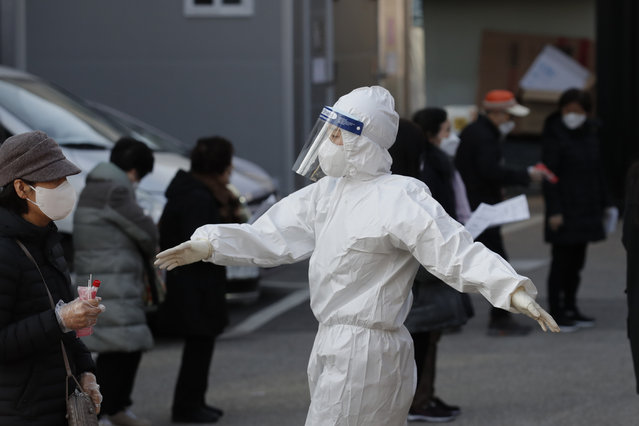 A medical worker wearing protective gear speaks as people wait in queue during testing for COVID-19 at a coronavirus testing center in Seoul, South Korea, Saturday, December 12, 2020. (Photo by Lee Jin-man/AP Photo)
