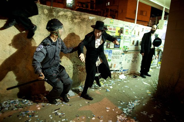Police arrest an ultra-Orthodox demonstrator in Jerusalem, on May 16, 2013. Tens of Thousands of ultra-Orthodox Israelis have clashed with police after gathering to protest against newly proposed government legislation that would see them drafted into the military.  (Photo by Uriel Sinai/Getty Images)