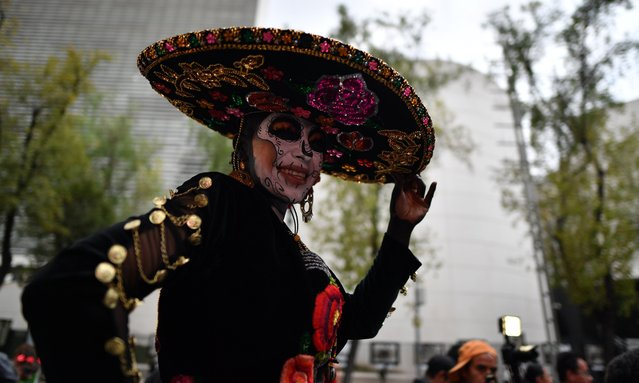 "A woman dressed as ""Catrina"" takes part in the ""Catrinas Parade"" along Reforma Avenue, in Mexico City on October 23, 2016. Mexicans get ready to celebrate the Day of the Dead highlighting the character of La Catrina which was created by cartoonist Jose Guadalupe Posada, famous for his drawings of typical local, folkloric scenes, socio- political criticism and for his illustrations of ""skeletons"" or skulls, including La Catrina. (Photo by Yuri Cortez/AFP Photo)"